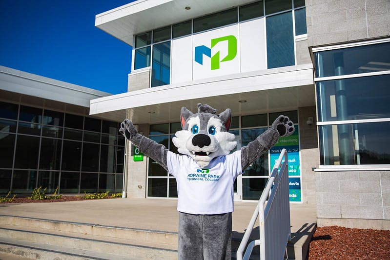 Photo of the Moraine Park Technical College mascot in front of a campus building