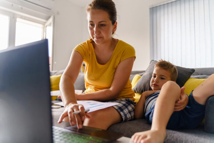 Woman sitting on the sofa at home working on documents while her son is lying beside her