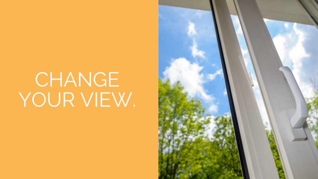 """Image of a glass window with green trees and blue sky outside and text that says, """"Change your view"""""""